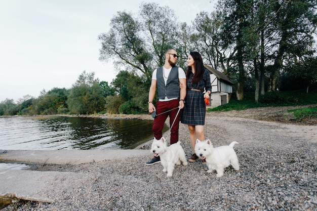 Husband with a beautiful wife walking their white dogs in the park