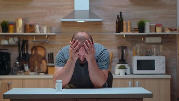 神経症の薬を服用している頭痛のある夫。片頭痛、うつ病、病気、めまい症状で疲れ果てた不安感に苦しんでいるストレスのたまった疲れた病気の心配している体調不良の人。