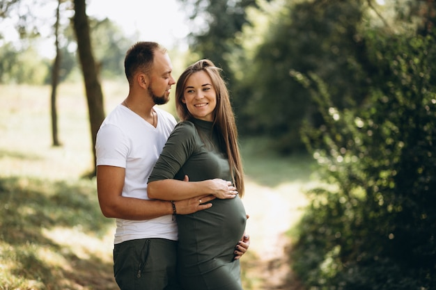 Husband with his pregnant wife walking in park