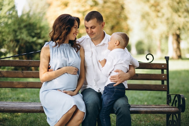Husband with pregnant wife and their son in park