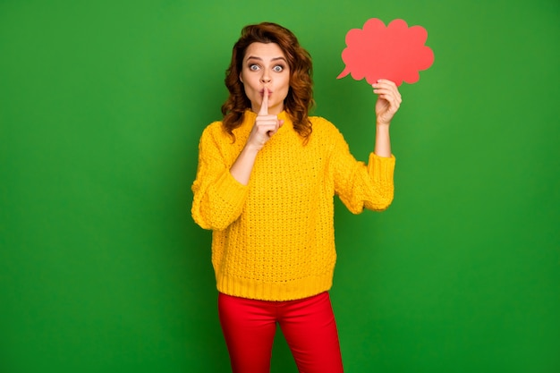 静けさは誰にも言わないでください!ファンキーな素敵な女性は赤い紙のカードを保持します吹き出し雲は信じられないほどのアイデアを拒否します共有機密ノベルティを着用ジャンパーズボン孤立した輝きの色の壁