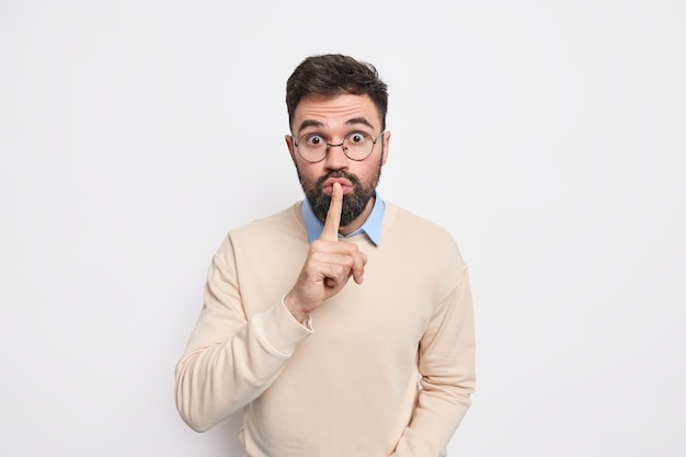 Hush do not say that. surprised bearded man presses index finger to lips asks not to spread false rumors stares shocked, makes taboo gesture wears spectacles and sweater poses indoor