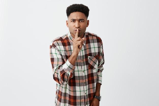 Тише. ты в библиотеке, а не дома. молодой симпатичный темнокожий ученик держит указательный палец перед губами с сердитым лицом, показывая детям, что они издают много шума.