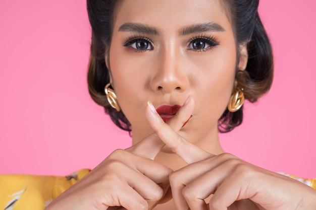 Губы и палец азиатской женщины красоты красные показывая знак безмолвия hush