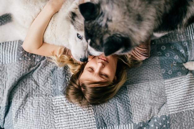ベッドに横になっている飼い主の顔をなめるハスキー子犬