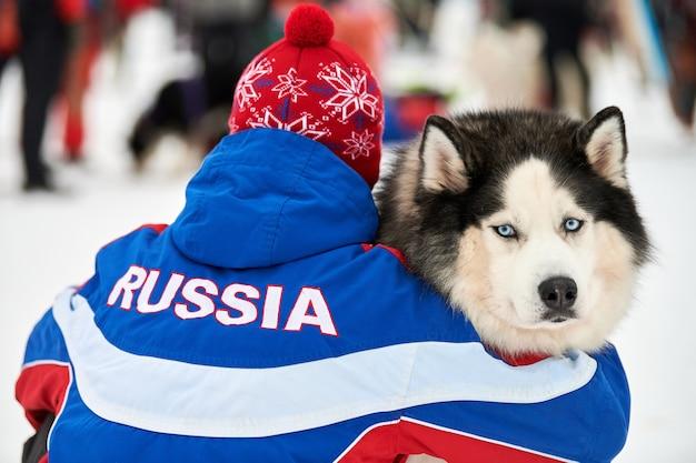 飼い主に抱かれたハスキーそり犬