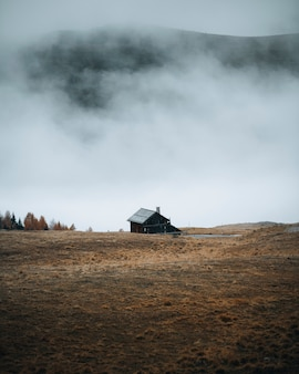 Hut by the curve road on a foggy hill