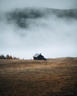 霧の丘のカーブした道のそばの小屋