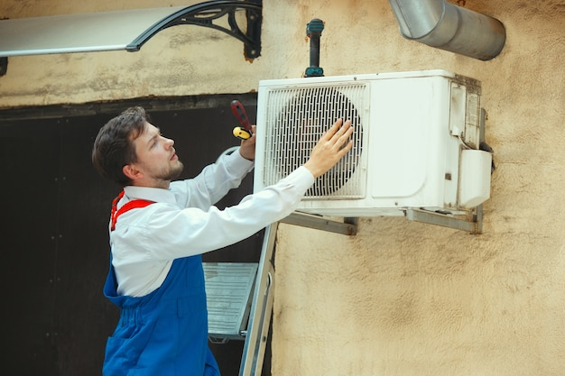 Hvac technician working on a capacitor part for condensing unit. male worker or repairman in uniform repairing and adjusting conditioning system, diagnosing and looking for technical issues.