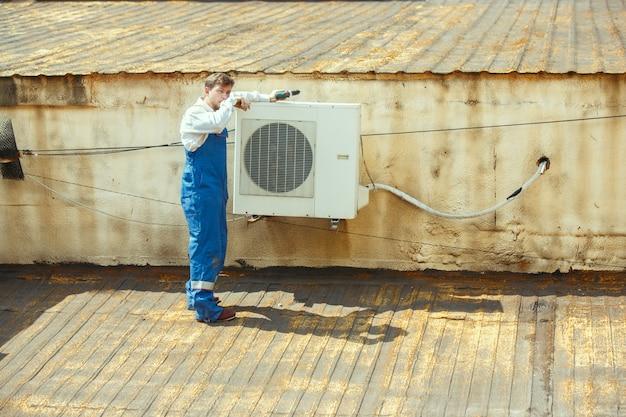 Техник hvac работает над конденсаторной частью для конденсаторной установки. мужчина-рабочий или ремонтник в униформе ремонтирует и регулирует систему кондиционирования, диагностирует и ищет технические проблемы.