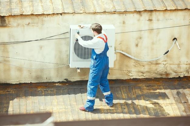 凝縮ユニットのコンデンサ部分に取り組んでいるhvac技術者。均一な修理と調整システムの男性労働者または修理工、技術的な問題の診断と検索。