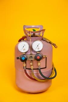 エアコン、センサーの燃料補給のための圧力計測定装置。黄色の背景にフレオンとシリンダー。 hvacのツール