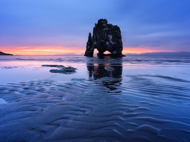 Утес хвицеркур на берегу океана в исландии. красивый пейзаж с отливом воды и видом на восходящее солнце