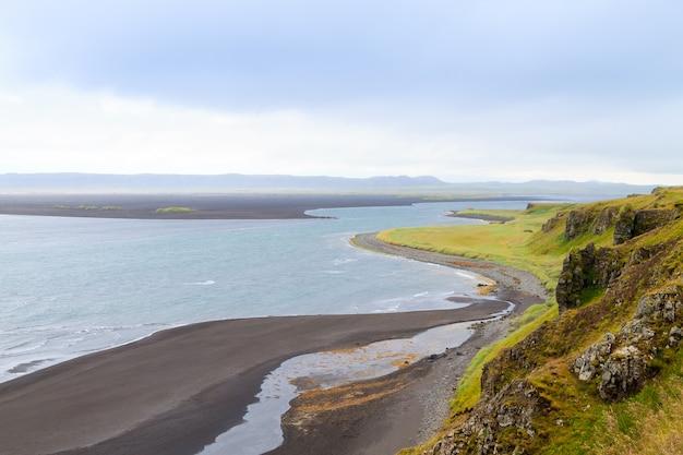 Морской стек хвицеркюр, исландия. пляж с черным песком. ориентир северной исландии