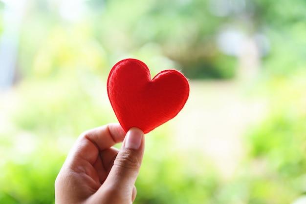 バレンタインの日に赤いハートを手で保持している女性または寄付は愛の暖かさを与えることに注意してください