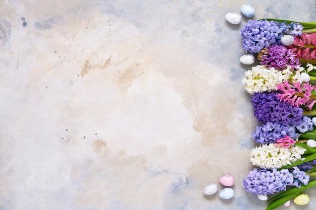 Цветы гиацинта и декоративные пасхальные яйца. копирование пространства, вид сверху.