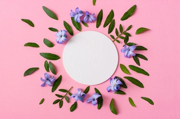 ピンクの背景にヒヤシンスの花と緑の葉。