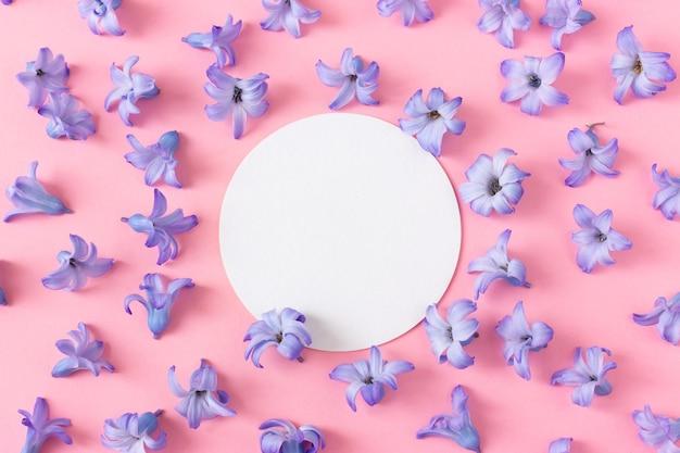 ピンクの背景にヒヤシンスの花。コースターのテキスト用の丸い空白のフレーム