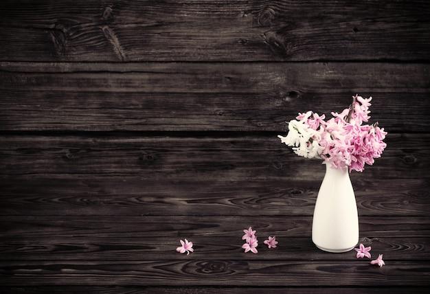 暗い古い木製の背景に白い花瓶のヒヤシンス