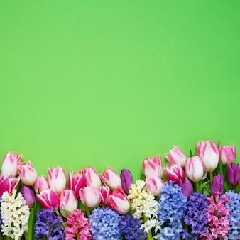 緑の背景にヒヤシンスとピンクのチューリップの花束。上面図、コピースペース。母の日、誕生日、国際女性の日、バレンタインデーのコンセプト。グリーティングカード。