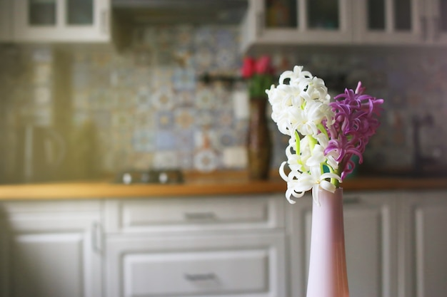 明るいキッチンを背景にしたヒヤシンス。テキストの場所。