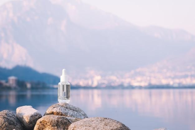Hyaluronic acid serum skincare glass bottle on stone mountain lake background serum product cosmetic