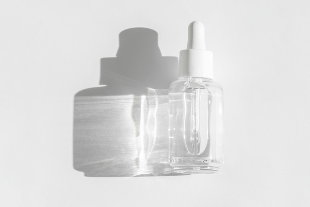 Hyaluronic or polyglutamic acid oil on white with sunlight and shadow. copy space Premium Photo