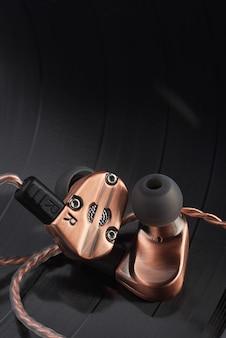 Hybrid dynamic driver balanced armature ear-buds on the lp vinyl record.