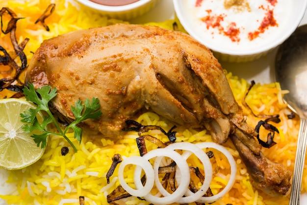 ハイデラバードチキンまたはダムビリヤニ、カダイまたはボウルにヨーグルトディップを添えて提供。セレクティブフォーカス