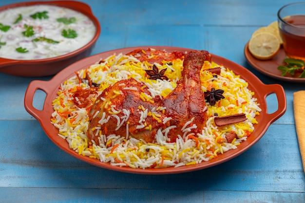 Цыпленок гидрабади бирьяни или цыпленок тандури с рисом басмати и раитой в качестве гарнира