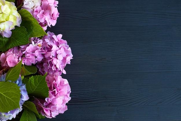 검은 나무 표면에 수국 꽃