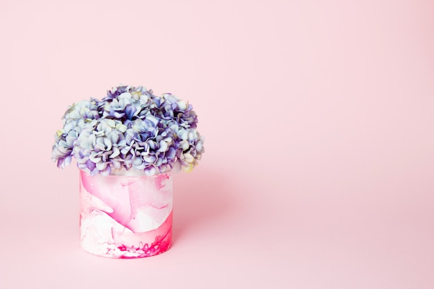Hydrangeas in a decorative abstract vase on pink