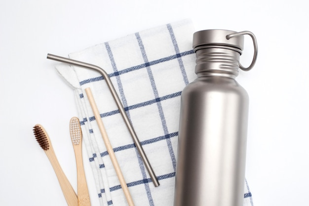 Hydration bottle and reusable stainless steel straws with bamboo toothbrushes. zero waste concept.