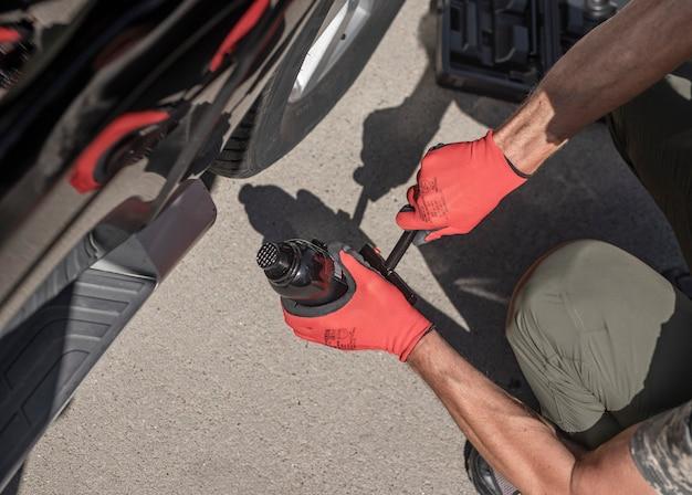 Гидравлический автомобильный домкрат помещается под автомобиль мужскими руками, вид сверху Premium Фотографии