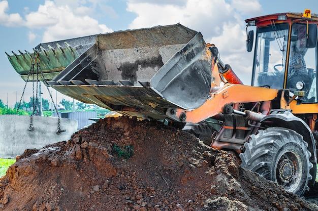 Гидравлическая поршневая система экскаватора с ковшом, опусканием в котлован на стальных тросах бетонного канализационного кольца. строительство или ремонт канализационного дома.
