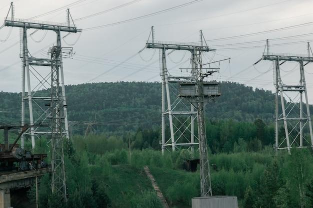 녹색 숲 배경에 수력 발전소 전력선