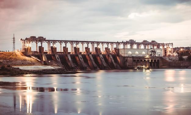 일몰에 강에 수력 발전소