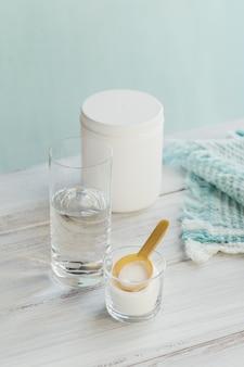ガラスのボウルと白い木製の背景の水で加水分解された海洋由来のコラーゲンペプチド。毎日のサプリメントの概念。