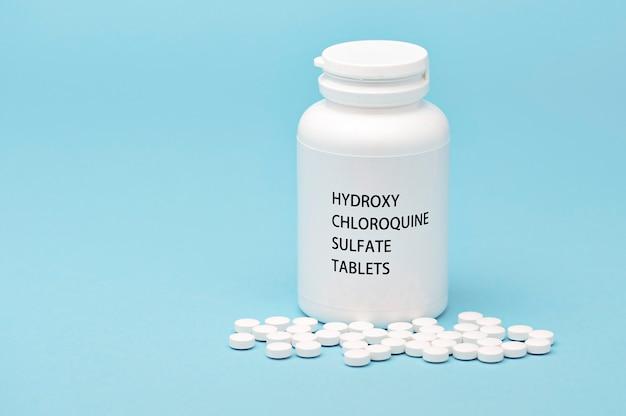 散在する丸薬が付いている白いびんの包装のhydroxychloroquine