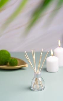 自宅のテーブルにヒュッゲとアロマテラピーのコンセプトキャンドルとアロマディフューザー