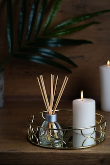 Hygge and aromatherapy concept -candles and aroma reed diffuser on table at home. high quality photo