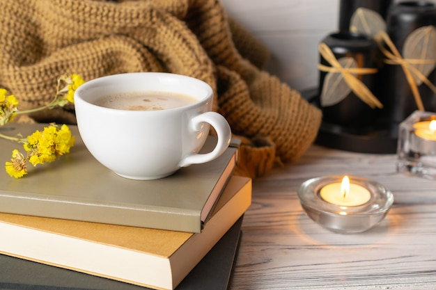 Hygge composition with coffee, candles, books and knitted plaid