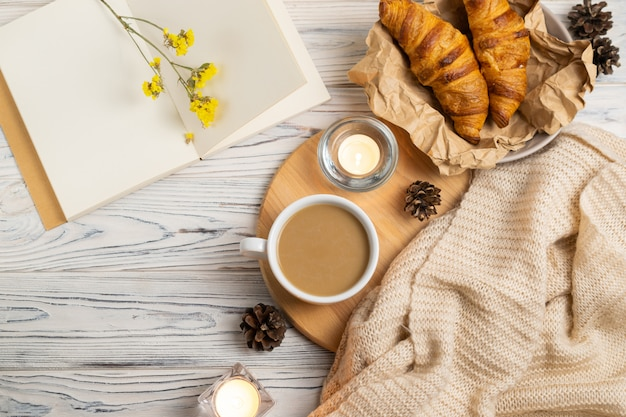 Hygge composition with coffee, candles, fresh croissants and knitted plaid. overhead flat lay