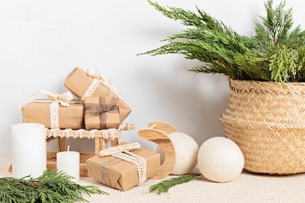 Hygge 친환경 종이 포장 선물 및 녹색 가지가있는 바구니. 스칸디나비아 크리스마스 제로 폐기물 장식 및 선물
