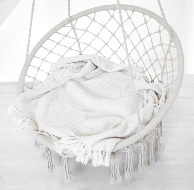 Hygge scene with white hammock chair with grey pillow. cozy place for weekend relax in the room.