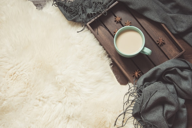 Hygge still life with cup of coffee, warm scarf on furskin.