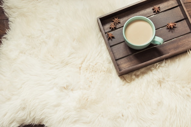 Hygge still life with hot cup of black coffee, warm scarf on furskin and wooden board.