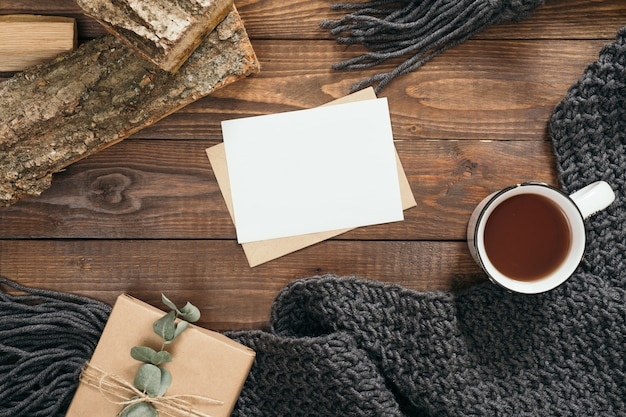 Hygge style flatlay composition with book, cup of coffee, fashion knitted scarf, firewood