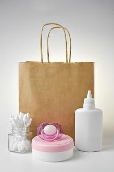 赤ちゃんのための衛生およびボディケア製品。おむつとパンティー、クリーム、おしゃぶり、タルカムパウダーを紙袋に入れて