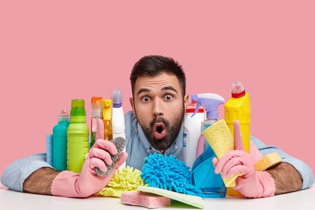 Hygiene, cleaning concept. surprised bearded guy with terrified expression, sits at table with bottles of detergents, sponges, keeps jaw dropped